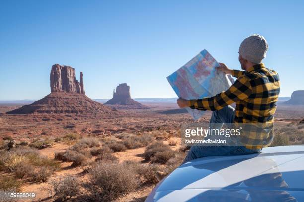 road trip concept; young man outside car looking at road map for directions exploring national parks and nature ready for adventure - southwest stock pictures, royalty-free photos & images