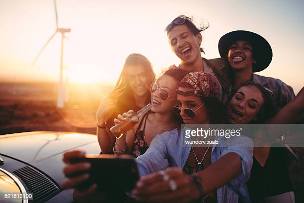 Road Trip hipster friends taking selfie during sunset with phone
