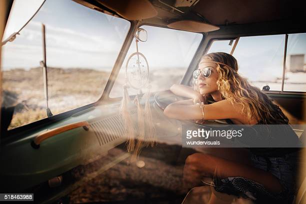 road trip hipster girl sitting in retro van at beach - hippie woman stock photos and pictures