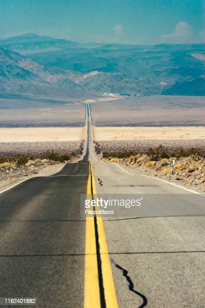 viagem de estrada nos eua-estrada no meio do deserto dentro do vale da morte - usa - fotografias e filmes do acervo