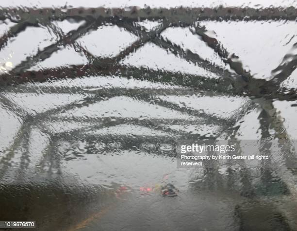 road view driving across a bridge in a rainstorm - barrier highway stock photos and pictures