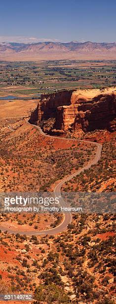 road winding downhill through red terrain - timothy hearsum stock pictures, royalty-free photos & images