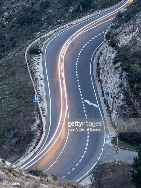 Road with a curve in the shape of s during the night, with lights of vehicles