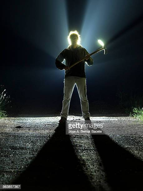 Road with a silhouette of a man with an ax