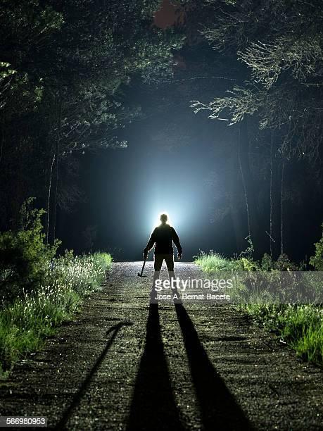 road with a silhouette of a man with an ax - assassino - fotografias e filmes do acervo