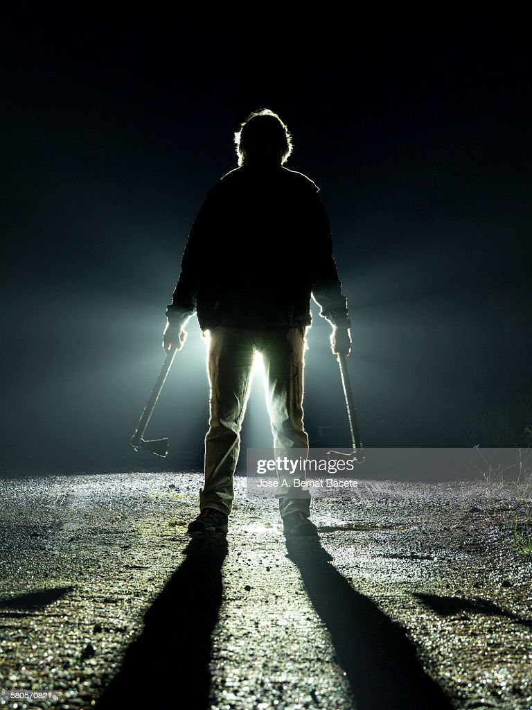 Road with a silhouette of a man with an ax : Stock Photo
