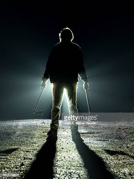 road with a silhouette of a man with an ax - back lit stock pictures, royalty-free photos & images