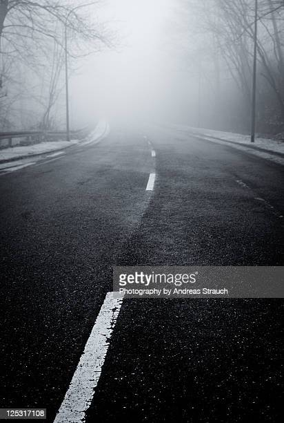 Road with fog in front and white strips on road