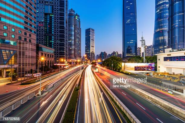 road with light trails and illuminated modern skyscrapers in background, lujiazui, shanghai, china - lujiazui stock photos and pictures
