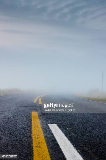 road with markings against sky during foggy weather - heinovirta stock pictures, royalty-free photos & images