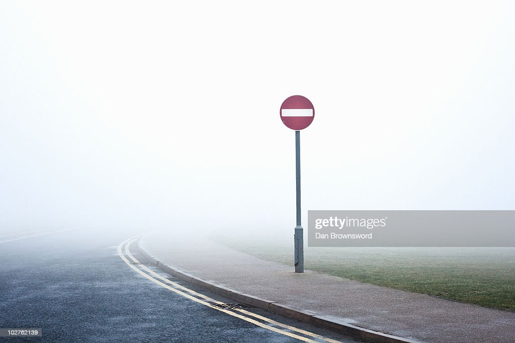 Road with no entry sign in fog : Stock Photo
