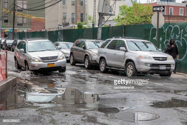 road with pot holes and puddles - pothole stock photos and pictures