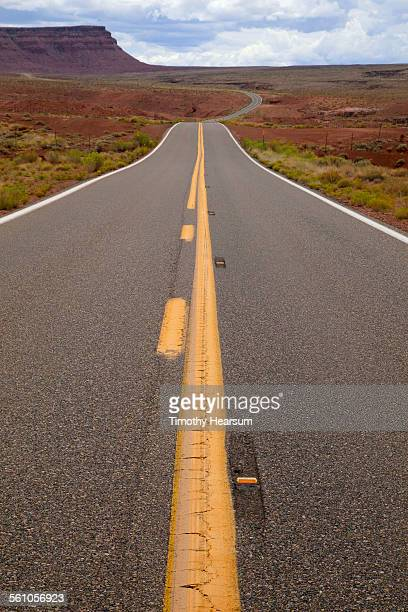 road with red mesa beyond - timothy hearsum stock photos and pictures