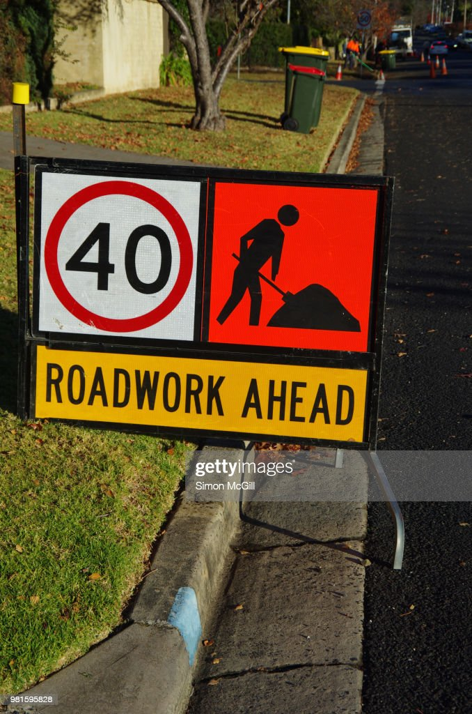 road work ahead manual worker ahead and 40 kilometer per hour speed limit signs on a suburban road