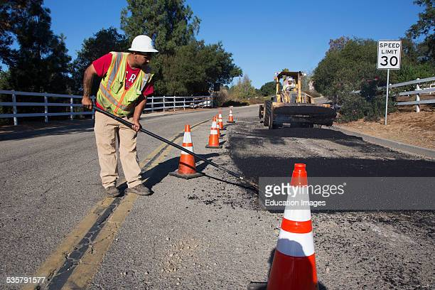 Road worker repaves road with steam Encino Drive Oak View California