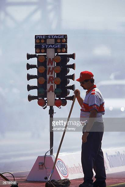 A road worker stands in front of the Christmas Tree Lights during the NHRA Summitracingcom Nationals at the Motor Speedway on April 8 2000 in Las...
