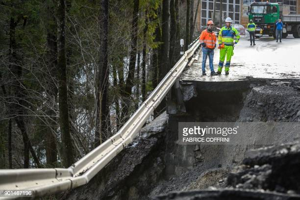 Road workers stand on the edge of the road reaching the Adelboden ski resort after it was swept away by a raininduced mudslide near Frutigen on...