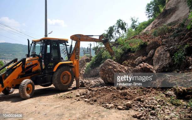 A lady clears debris near Peer Kho Temple following a landslide on the outskirts of Jammu on September 25 2018 in Jammu India