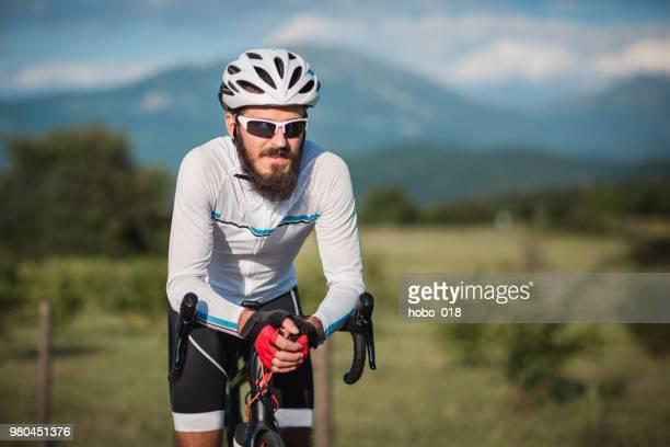 racefiets man een pauze nemen van rijden - wielrennen stockfoto's en -beelden