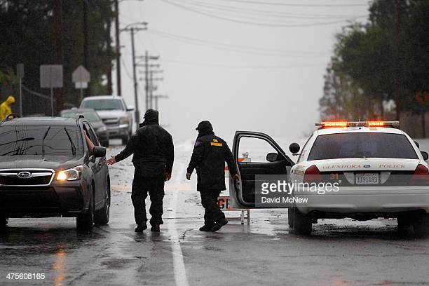 A roadblock keeps people from entering an evacuated neighborhood below the Colby Fire burn area as a storm brings rain in the midst of record drought...
