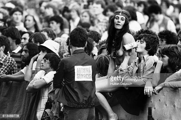 A roadie chats with one of the young fans leaning against a barrier at the annual Knebworth Rock Festival