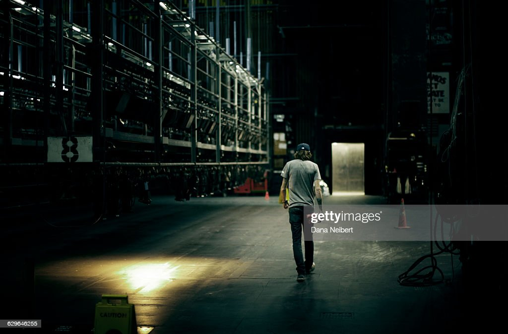 A roadie walks back stage : Stock Photo