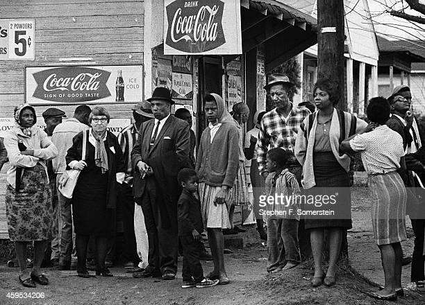 Roadside bystanders watching the Selma to Montgomery civil rights marchers pass by Coca Cola signs on stores On March 25 1965 in Montgomery Alabama
