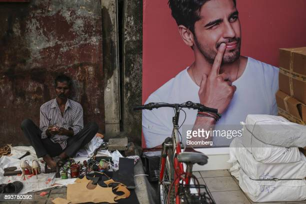 A roadside cobbler sits next to an advertisement in Mumbai India on Friday Dec 15 2017 India's inflation surged past the central bank's target...