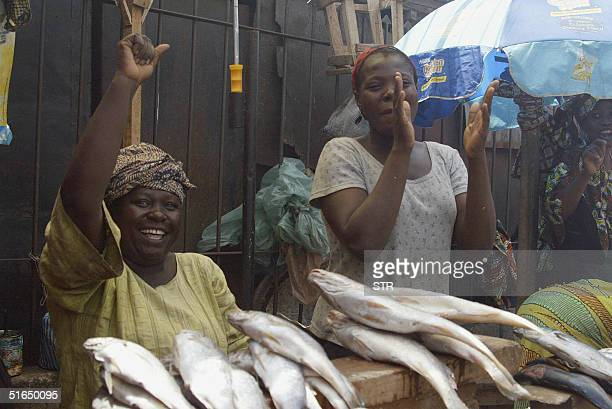 Roadside fish vendors celebrate as President of the Nigeria Labour Congress Adams Oshiomhole arrives to address the public 03 November 2004 during a...
