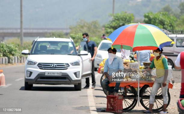 Roadside fruit vendors under the shade of an umbrella while waiting for customers on a hot summer day on May 27, 2020 in Jammu, India.