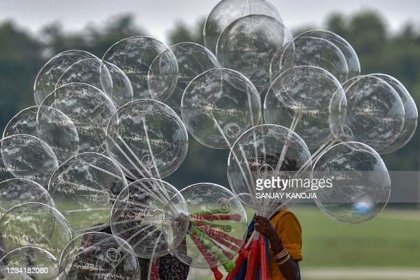 Roadside hawkers carry balloons to sell in Allahabad on July 25, 2021.