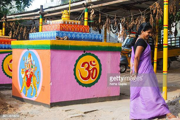 CONTENT] A roadside hindu temple an Indian lady in matching lavender sari