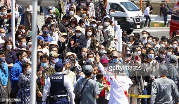 Roadside is jammed with people watching the Tokyo Olympic torch relay in Katsuragi in Nara Prefecture, western Japan, on April 11 amid the...