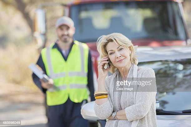 Straßenrand Mechaniker hinter Frau auf Handy