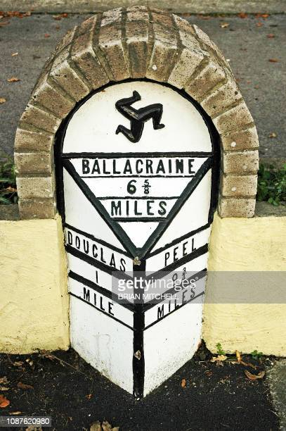 roadside milestone showing distance to towns in miles, united kingdom - isle of man stock pictures, royalty-free photos & images