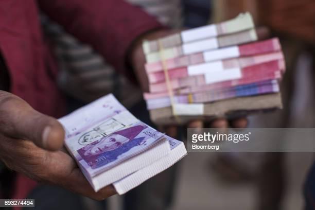 A roadside money changer handles bundles of Pakistani rupee banknotes at a currency exchange market in Karachi Pakistan on Thursday Dec 14 2017...