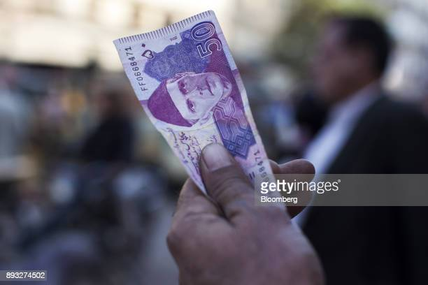 A roadside money changer holds up a Pakistani Fifty Rupee banknotes attempting to attract customers at a currency exchange market in Karachi Pakistan...