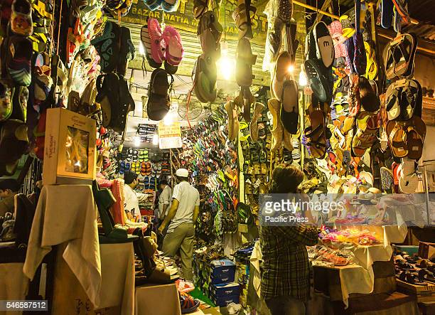 Roadside shoe shop at Delhi is displayed with various products on the occasion of Eid-ul-Fitr festival in the night before the morning prayer. People...