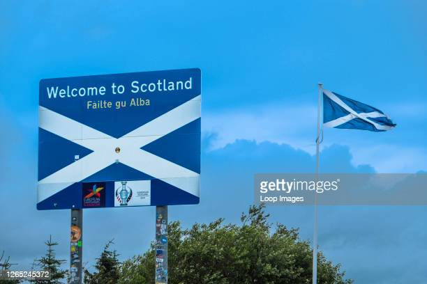 Roadside sign and cross of St Andrew flag welcoming visitors to Scotland at Carter Bar.