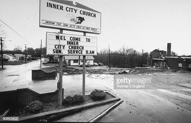 Roadside sign emblazoned w INNER CITY CHURCH WELCOME TO INNER CITY CHURCH SUN SERVCE 11AM leading to empty lot rubble of remains of the church after...