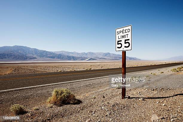 roadside sign in desert landscape - speed limit sign stock photos and pictures