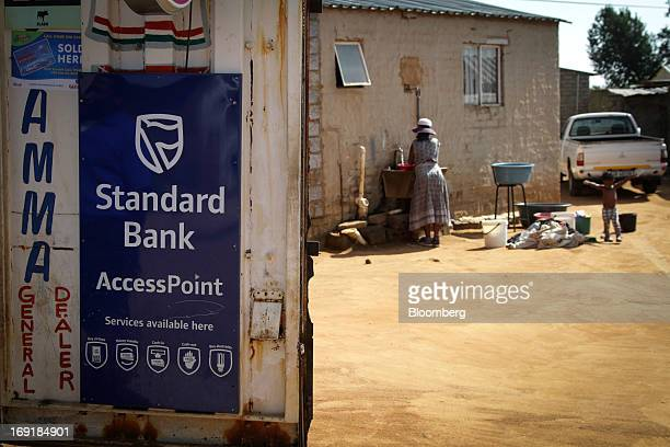 A roadside store advertises an access point for the MPesa mobile phone money transfer service operated by Standard Bank Group Ltd in Tembisa near...