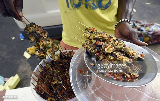 A roadside vendor prepared peppered snails snack in the southern Nigeria town of Uyo Akwa Ibom State on Novermber 7 2014 AFP PHOTO/PIUS UTOMI EKPEI