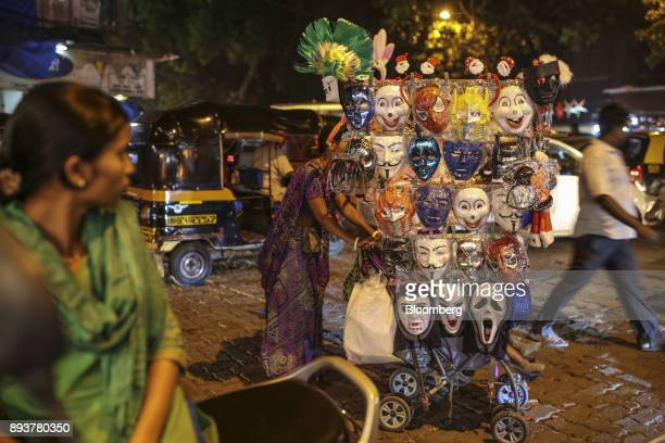 A roadside vendor pushes a cart filled with costume masks in Mumbai India on Friday Dec 15 2017 India's inflation surged past the central bank's...