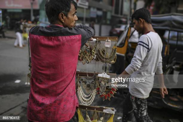 A roadside vendor selling necklaces waits for customers in Mumbai India on Friday Dec 15 2017 India's inflation surged past the central bank's target...