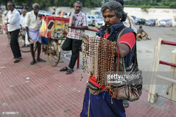 Roadside vendor stands with necklaces draped over his arm outside the Brihadeshwara Temple in Thanjavur, Tamil Nadu, India, on Sunday, Oct. 16, 2016....