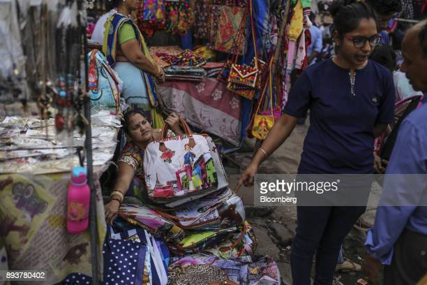 A roadside vendor waits for customers at a market in Mumbai India on Friday Dec 15 2017 India's inflation surged past the central bank's target...