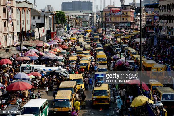 Roadside vendors display wears on major roads and vying for space with public transport as people shop ahead of the festive seasons at Idumota in...