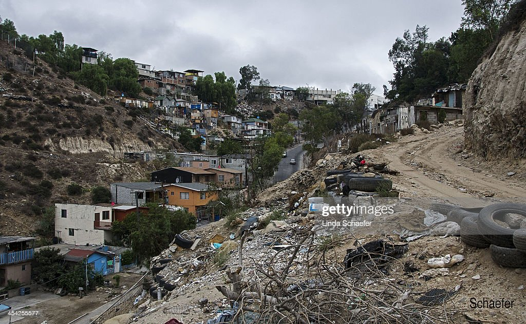 CONTENT] Roadside view of a poor section of Tijuana known for drug dealing. The winding dirt road led through the hillside dotted with houses of assorted constructions. Rubber tires lined the roadside.