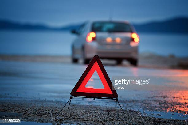 A roadside warning triangle and car with lights on wet road